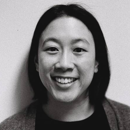 A black and white headshot of a woman smiling with medium length black hair wearing a black t-shirt and a gray cardigan.