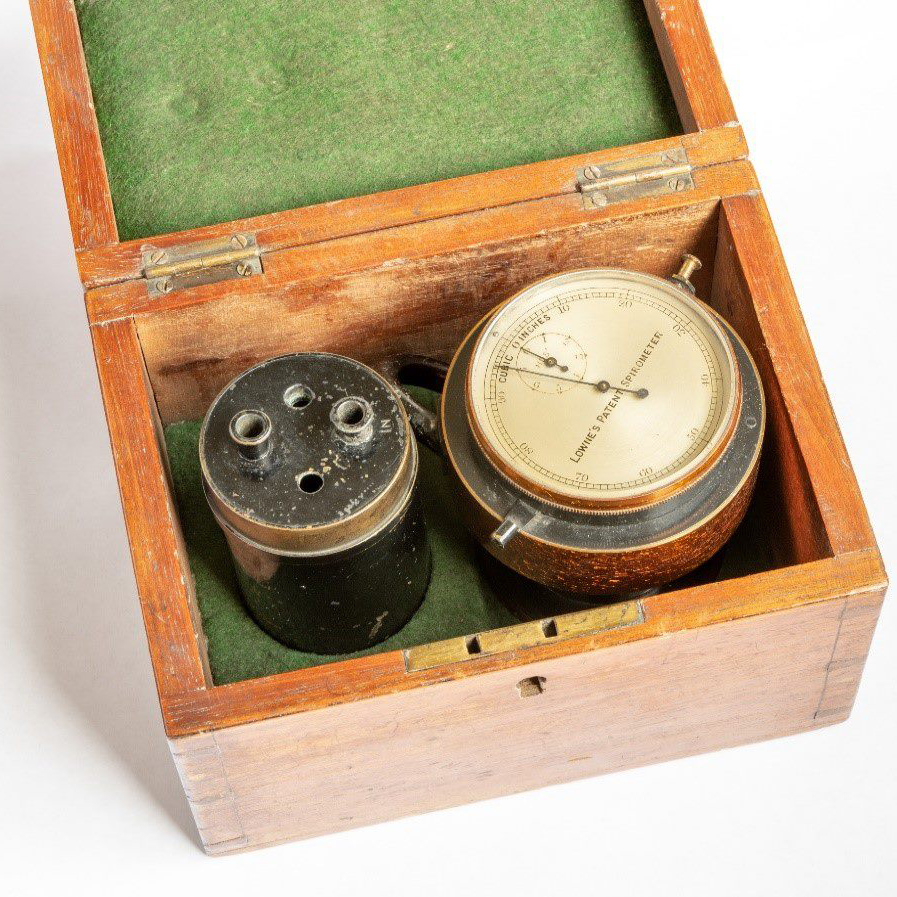 A wooden box lined with green fabric. Inside are two round devices. One is black with four holes at the top. One is white and brown with a meter at the top.